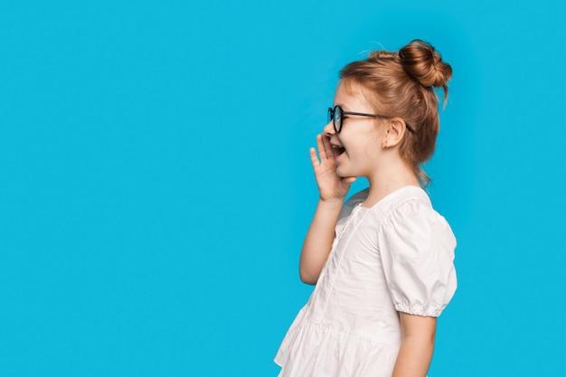 작은 소녀는 안경과 흰색 드레스를 입고 여유 공간이있는 파란색 스튜디오 벽에 비명을 지르고 있습니다.