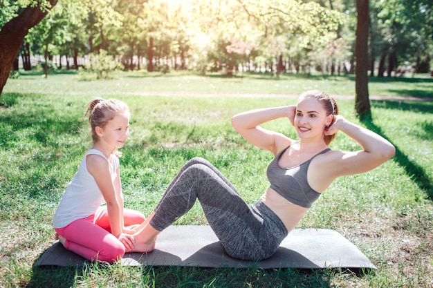 Small girl is sitting on carimate and holding feet of her mom while woman is doing some abs excercises. she is kepping her hnds close to hand. yoga and pilates concept.