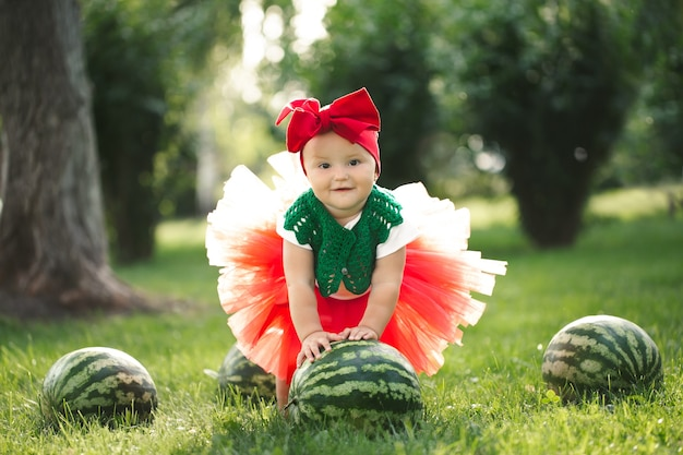 Small girl is sitting on the green grass in a red tulle skirt with watermelons.