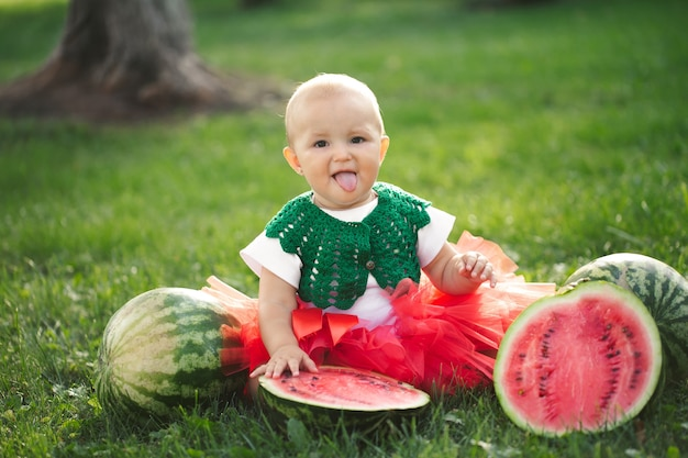 작은 소녀는 수박과 빨간색 얇은 명주 그물 치마에 푸른 잔디에 앉아있다.