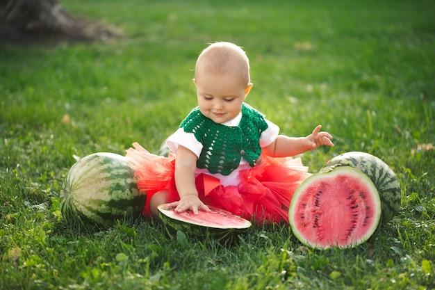 Маленькая девочка сидит на зеленой траве в красной тюлевой юбке с арбузами.