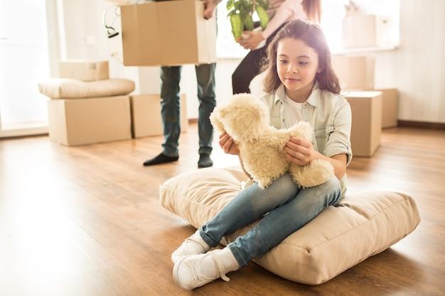 Маленькая девочка сидит на подушке на полу и смотрит на свою игрушку-мишку