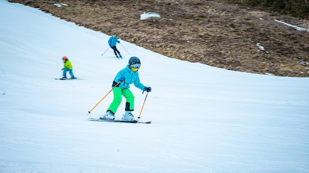 Маленькая девочка учится кататься на лыжах с лыжными палками
