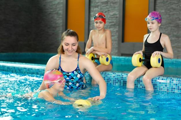 Маленькая девочка учится плавать в бассейне и плавает с гантелями из пеноматериала.
