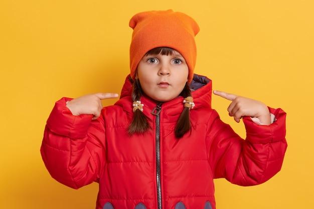 작은 소녀는 큰 눈으로 정면을보고, 검지 손가락으로 그녀의 뺨을 가리키며, 노란색 벽 위에 고립 된 그녀의 입술로 재미있는 얼굴을 찡 그리기