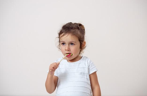 Маленькая девочка на ярком фоне стоит и ест леденец.