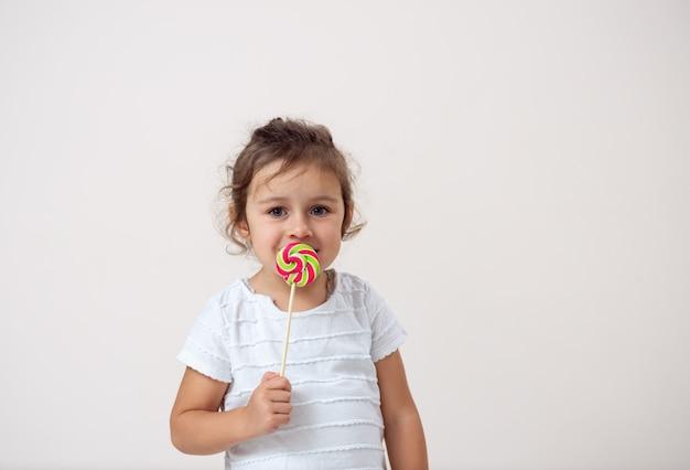Маленькая девочка на ярком фоне стоит с леденцом перед лицом.
