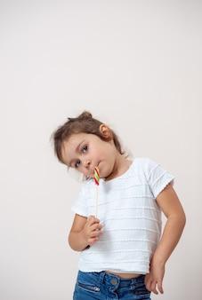Маленькая девочка на светлом фоне стоит, прислонившись к стороне, с леденцом у рта. изолированный.