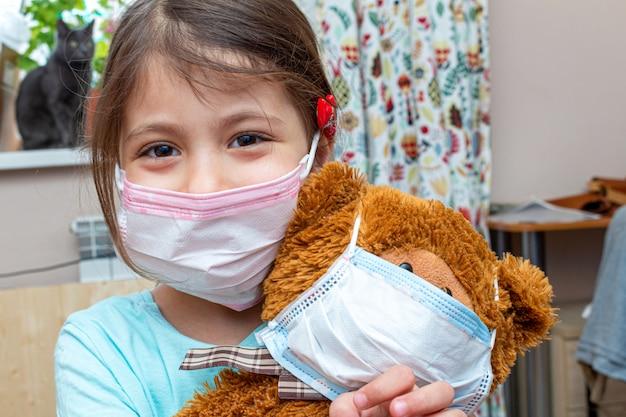 検疫隔離中に医療用防護マスクでおもちゃのクマを遊んでいる小さな女の子