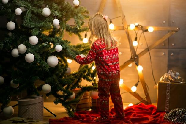 Small girl in pyjamas by the christmas tree