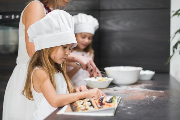 Маленькая девочка, читающая книгу рецептов, пока мать и сестра готовят еду