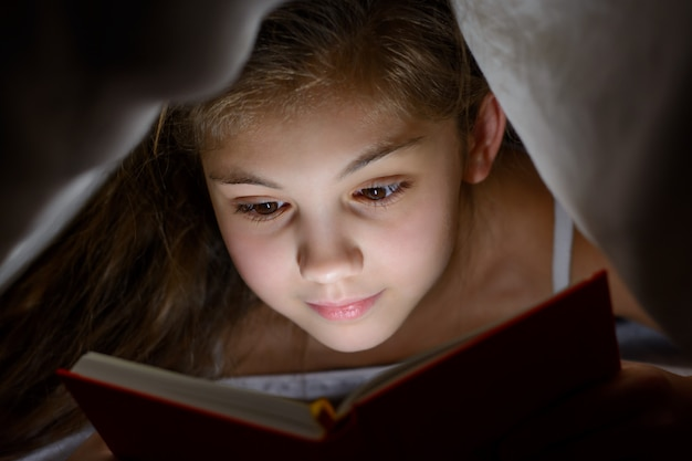 Small girl reads book with a flashlight under the blanket in bed