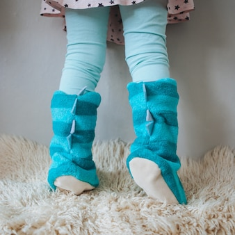 Small girl's legs in blue home slippers against the wall