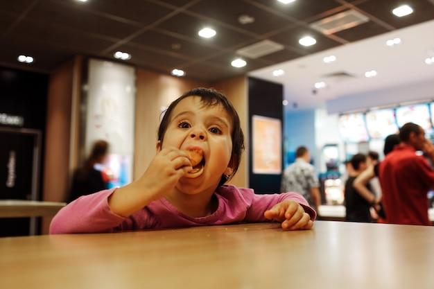 작은 소녀는 tabel에 혼자 앉아 카페 또는 레스토랑에서 식사를합니다. 열린 입에 식사를 넣으십시오.
