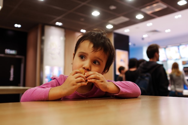 Small girl sit alone at tabel and eat meal in cafe or restaurant.