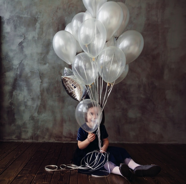 The small girl sits on the floor and keeps ballons in the room