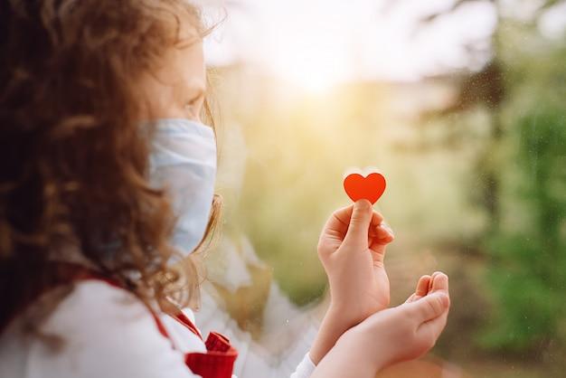 小さな赤いハートの窓枠に座っている小さな女の子は、コロナウイルスcovid-19の流行中に病院で働いている医師や医療スタッフに感謝する看護師に感謝を示す方法を示しています。セレクティブフォーカス