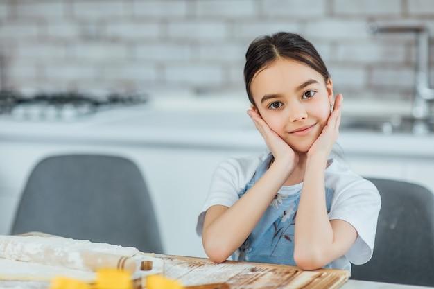 台所の前で笑っている小さな女の子