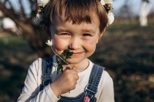 The small girl sniffs a flower
