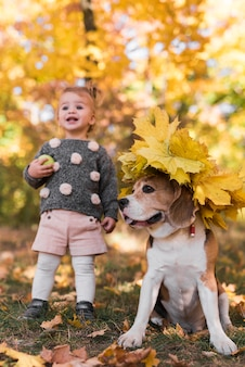 Small girl standing near beagle dog wearing autumn leaf hat in forest