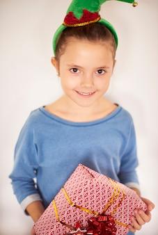 Small girl standing with christmas box