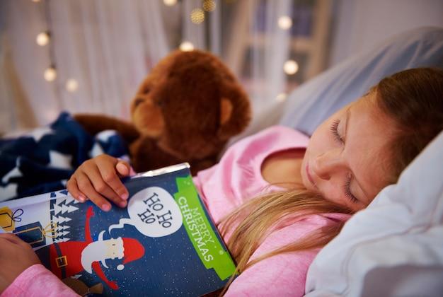 Piccola ragazza schiacciando un pisolino con il libro e l'orsacchiotto