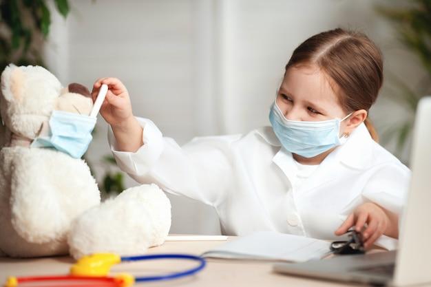 Маленькая девочка в белом пальто и маске, измеренная температура плюшевого мишки.
