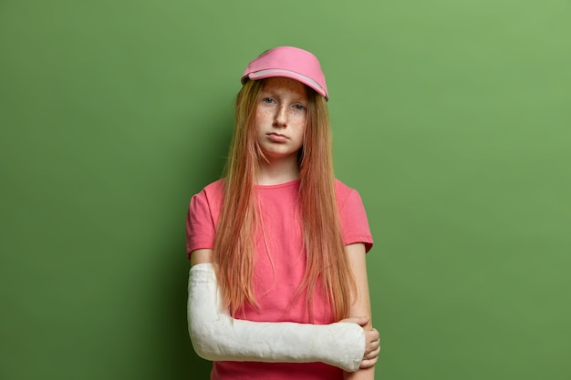 Small girl with broken arm in cast, hurting sad face expression, wears cap and casual t shirt, has problems with bones, freckled skin, isolated on green wall. children and injuries concept