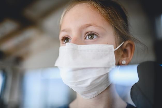 自宅で屋内でフェイスマスクを持つ小さな女の子