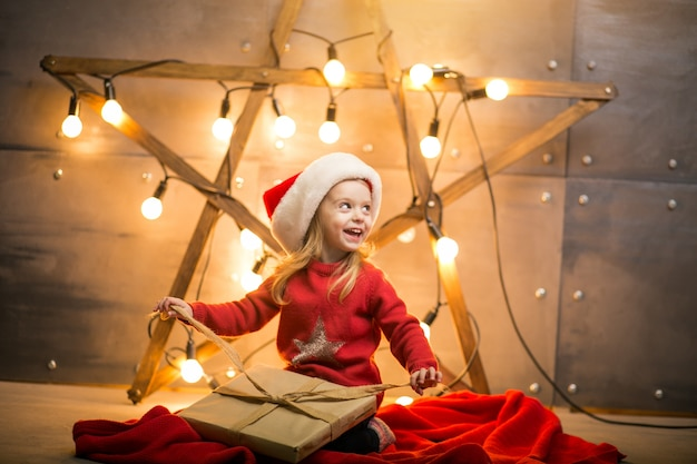 Small girl with gifts on christmas sitting on red blanket by the star
