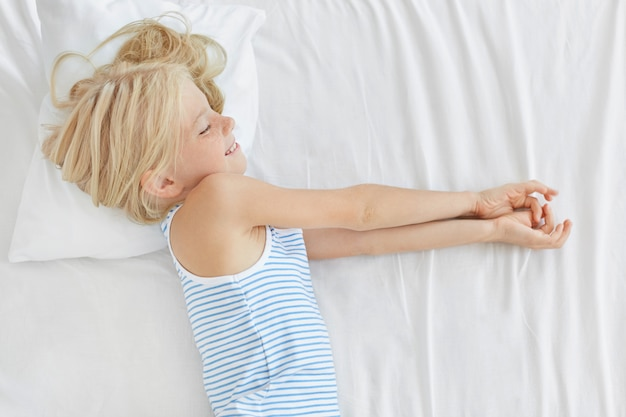 Small girl with light hair having good night on white bedclothes, dreaming about something, smiling pleasantly. girl having dreams in bed. children, childhood, relaxation and lifestyle concept