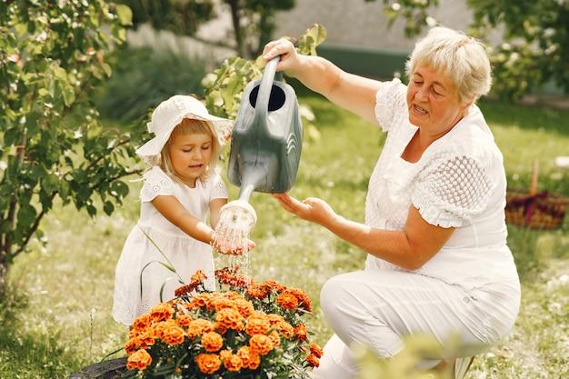 Piccola ragazza con la nonna senior giardinaggio nel giardino sul retro. bambino in un cappello bianco.