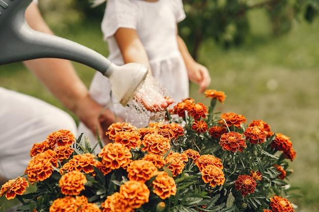 裏庭の庭でガーデニングをしている先輩の祖母と小さな女の子。白い帽子をかぶった子供。