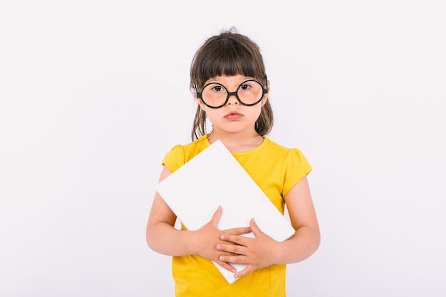 Маленькая девочка с серьезным жестом в желтой футболке и круглых черных очках держит белую бумагу в руках на белом фоне