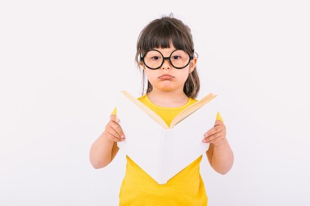 Маленькая девочка с серьезным жестом в желтой футболке и круглых черных очках держит в руках открытую белую книгу на белом фоне