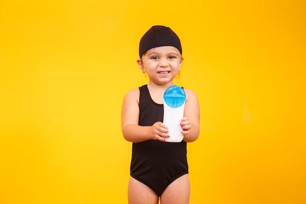 수영 수영복과 자외선 차단제를 가진 작은 소녀