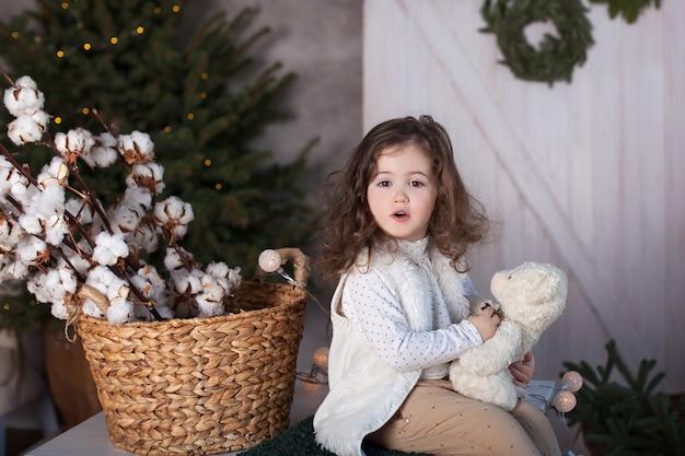 Small girl with teddy bear on christmas