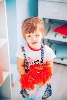 おもちゃの人形を笑顔で小さな女の子