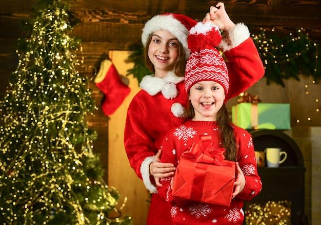 ホリデーギフトを準備する小さな女の子。プレゼントを受け取る。姉妹と家族。妹へのクリスマスプレゼント。子供たちの小さな陽気な女の子はギフトボックスを保持します。ボクシングデー。家族への贈り物を選ぶ子供たち。