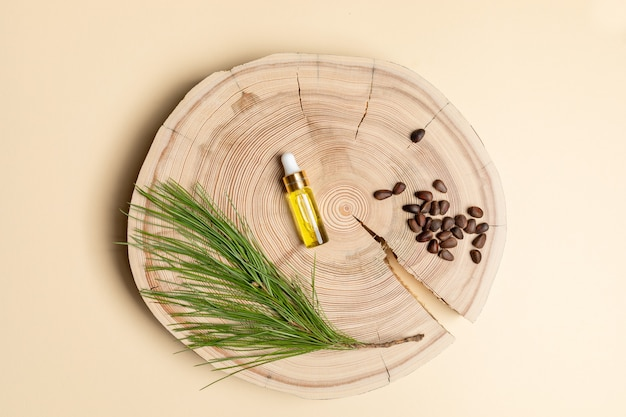 Small glass bottle with coniferous spa aromatic essential cedar oil, branch, nuts on wooden saw cut in center of beige backdrop. christmas aromatherapy and spa concept. view from above, copy space.