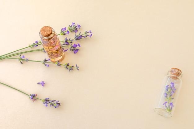 복사 공간이 있는 베이지색 배경에 필수 라벤더 오일과 라벤더 잔가지가 든 작은 유리병. 식물성 화장품 개념