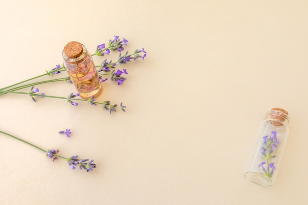 Small glass bottles with essential lavender oil and sprigs of lavender on a beige background with copy space. botanical cosmetics concept