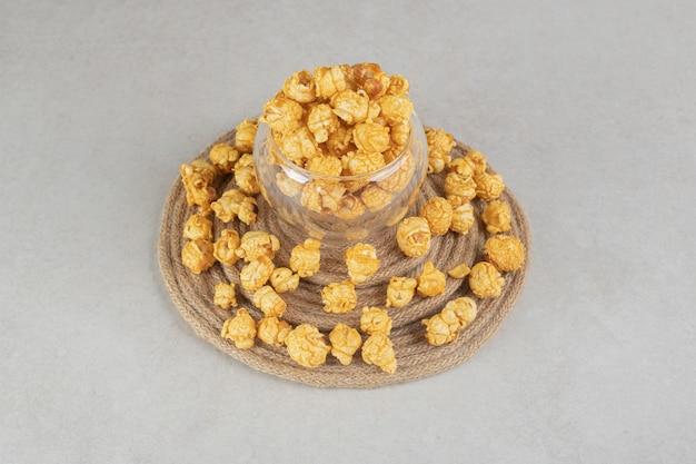 Piccola ciotola di vetro su un sottopentola lavorato a maglia circondato da popcorn ricoperto di caramello su marmo.