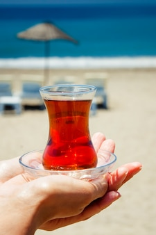 Small glass cup with tea on the background of the blue sea,  beach and beach umbrellas.