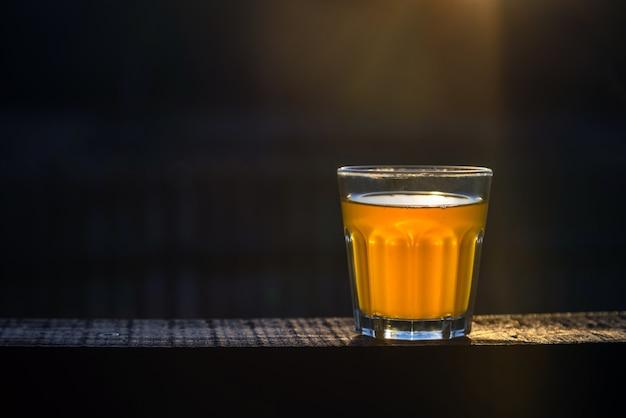 외부 나무 판자에 거품이없는 수제 맥주 한 잔.