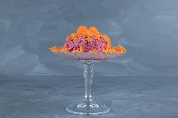 대리석 테이블에 당근을 얹은 호두와 비트 샐러드의 적당한 부분이있는 작은 유리 받침대.