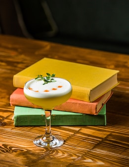 A small glass of vanilla milk cocktail on a wooden table with books around.