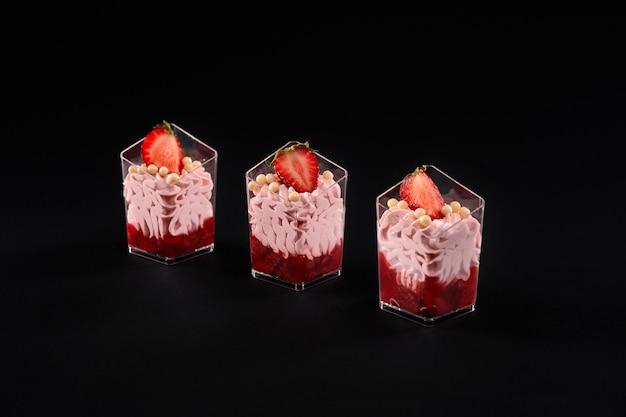 휘핑 핑크 크림과 딸기로 장식 된 레드 잼으로 채워진 작은 잔