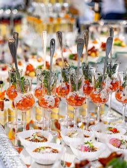 Маленькие стаканы с закусками за столом. соленые закуски на праздник. сырье с хрустальными бокалами. крупный план.