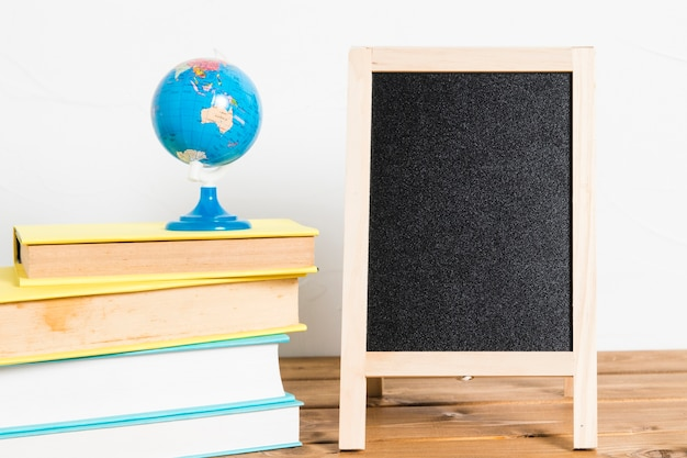 木製のテーブルに空の黒板と本の小さなグローブ